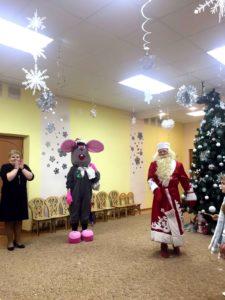 Дед Мороз приплясывает около елки